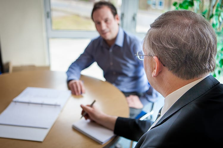 Two business men talking at desk with one making notes