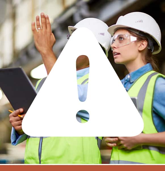 White warning triangle sign icon overlaying a photo of two construction workers discussing