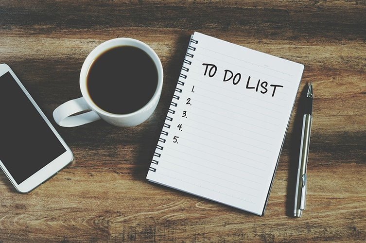 Top view of mobile phone, coffee cup, pen and note pad saying to do list on wooden surface