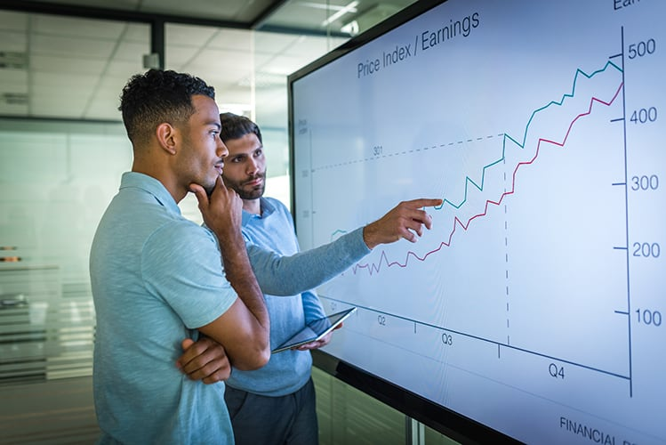 Two men looking at large screen with image of a price graph