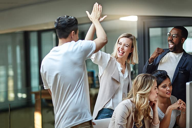 Shot of a group of colleagues giving each other a high five while using a computer together at work