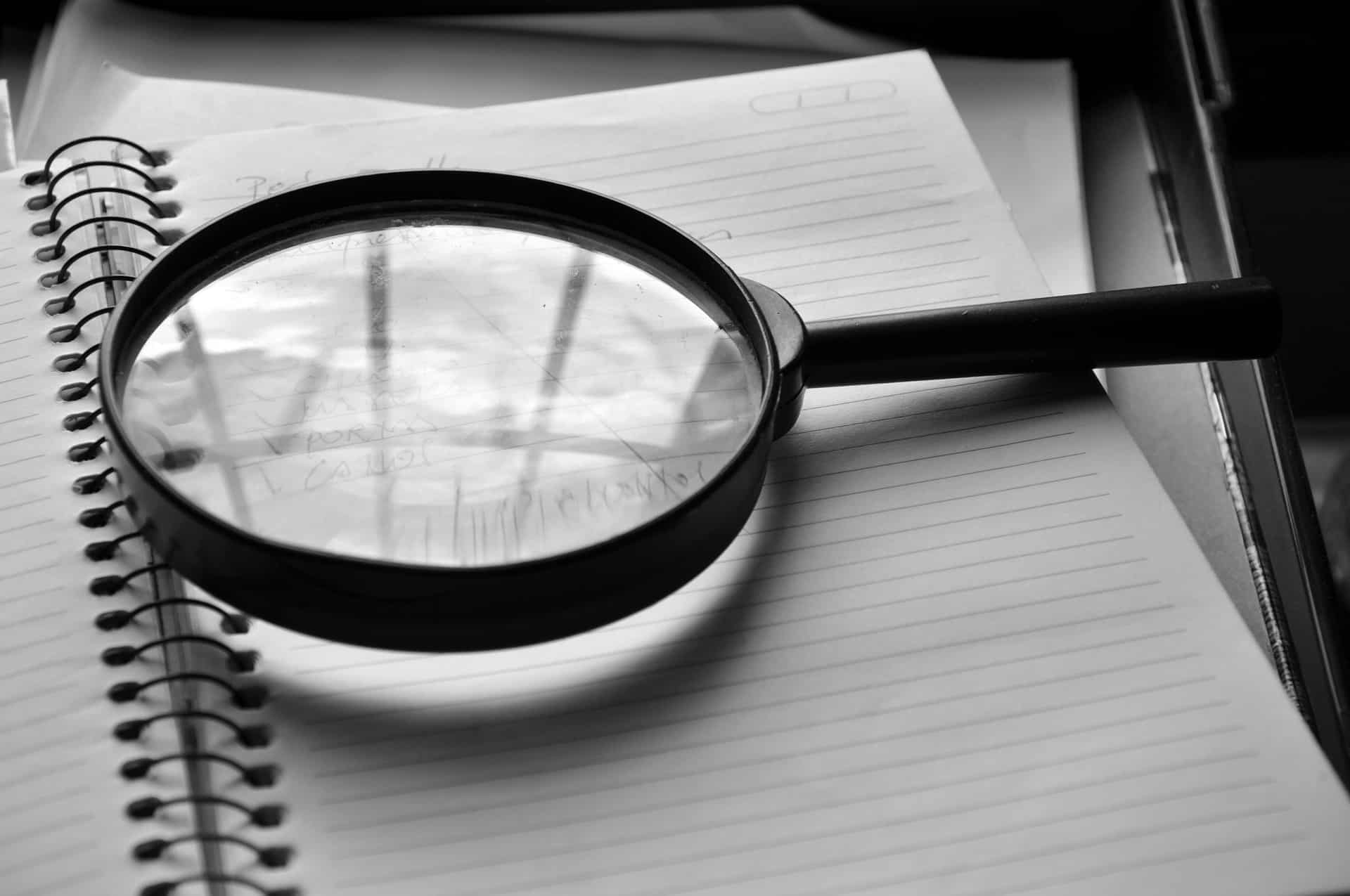 Magnifying glass on a notepad