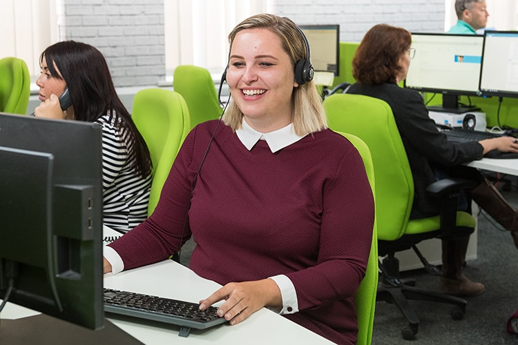 Lady smiling and sitting at a desk in call centre