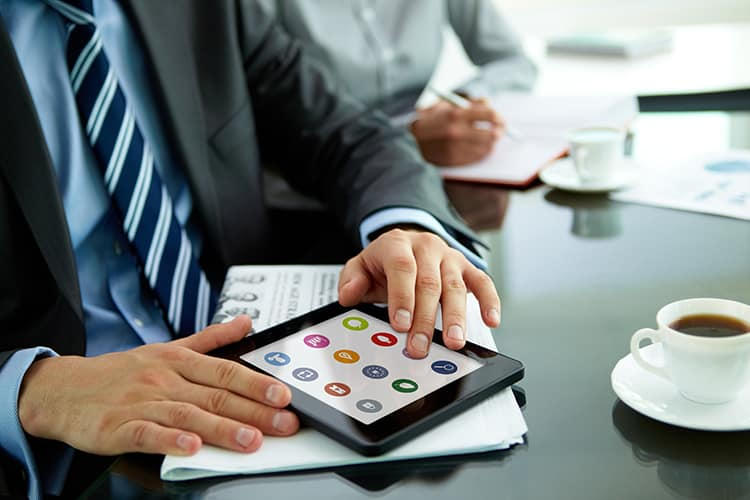 Man working at office desk with tablet and coffee