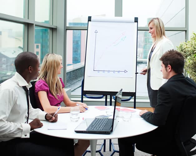Lady with flip board presenting to people sat at a desk