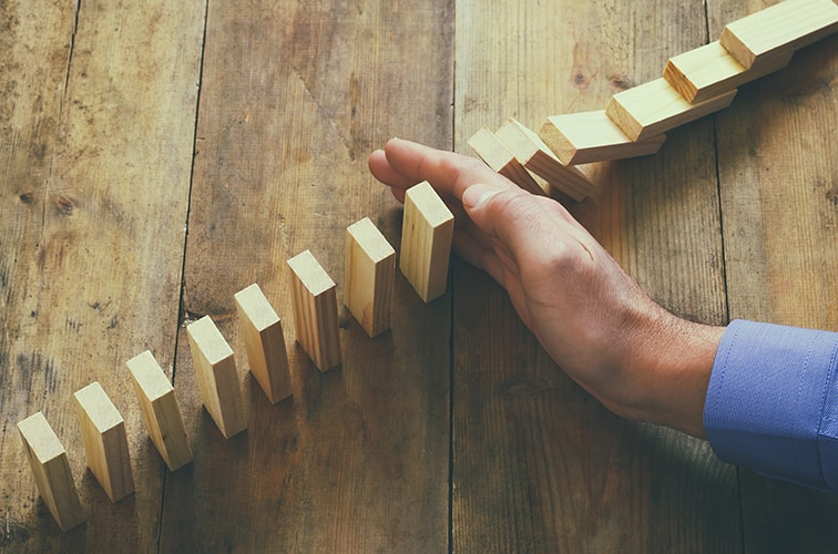 Hand pushing over row of dominos