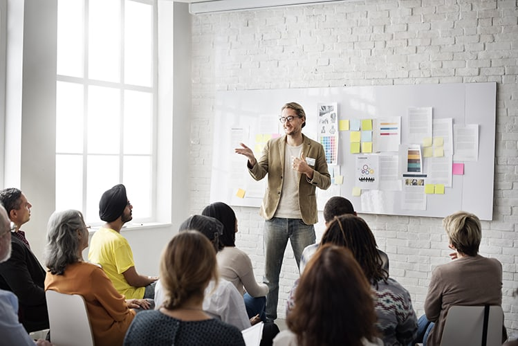 Man presenting to room of people sitting on chairs