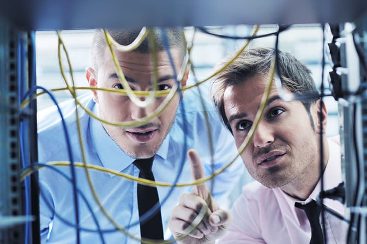 Two men looking at tangled data wires