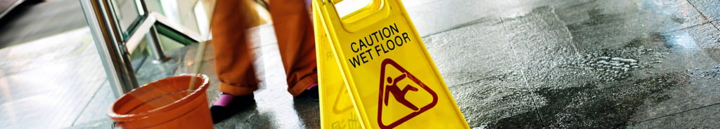 Person cleaning floor with bucket and mop with a wet floor sign