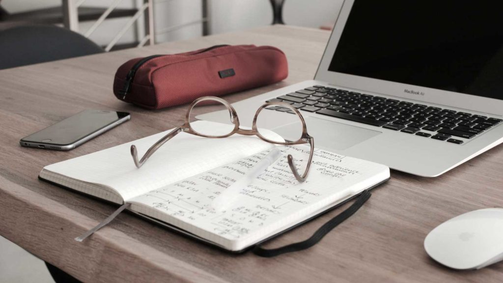 Glasses, phone, pencil case, notepad and laptop on desk