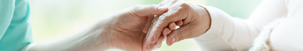 Carer holding an old person's hand