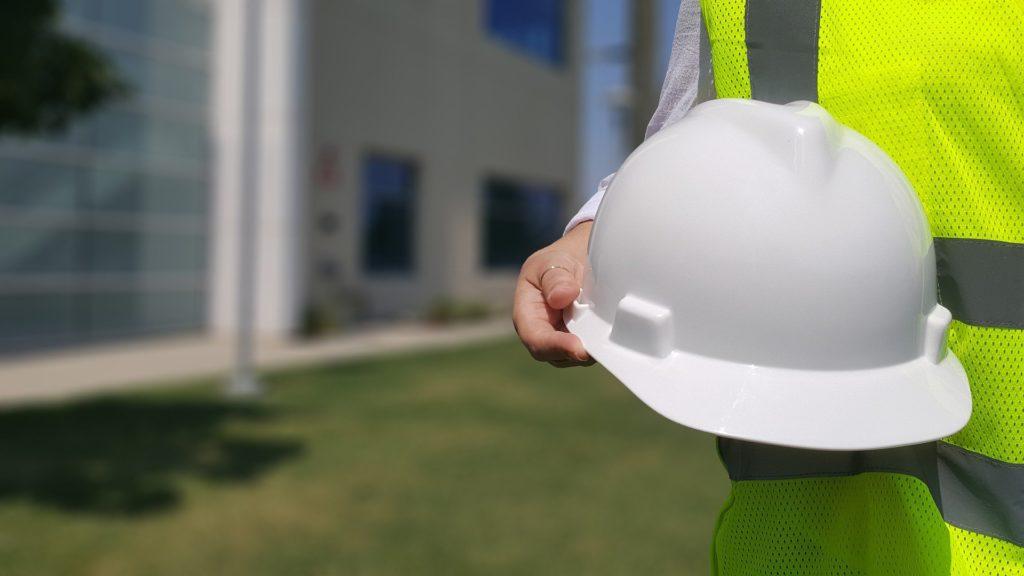 Person in high visibility jacket holding a hard hat