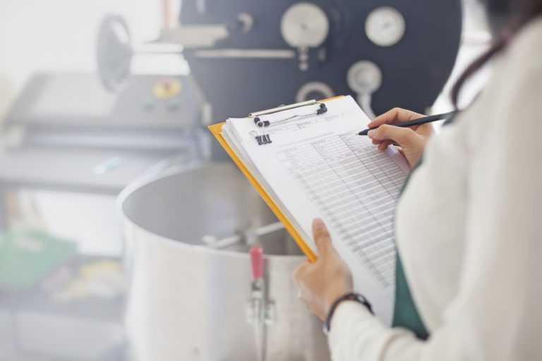 Woman in lab writing on a chart