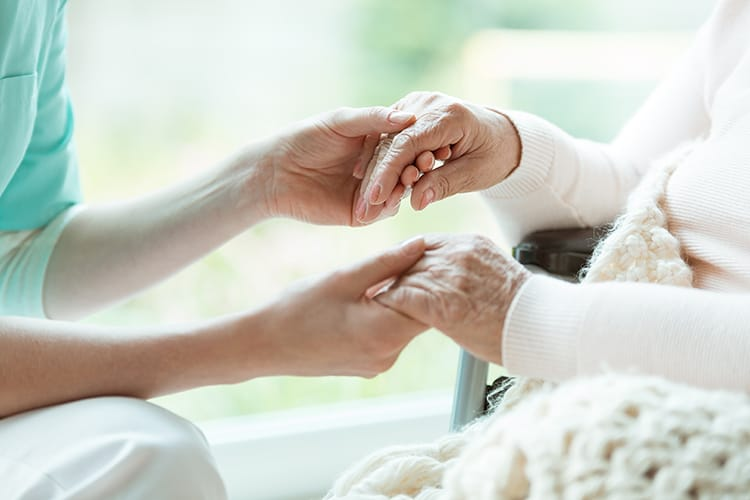 Carer holding an elderly person's hands