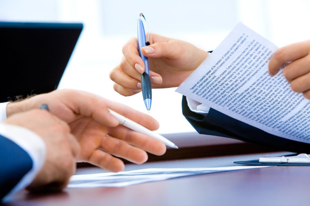 Two sets of hands holding a pen and paper