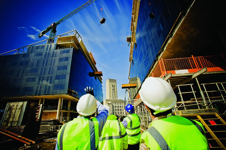 Construction workers standing in front of building under construction