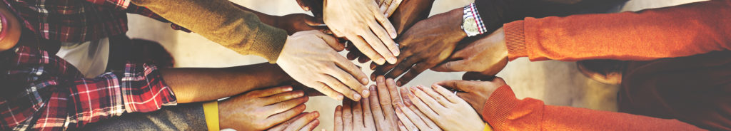 Young people in a circle putting hands together
