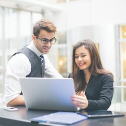 man and woman in office smiling at laptop