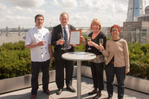 Two men and two women holding champagne glasses on roof top garden