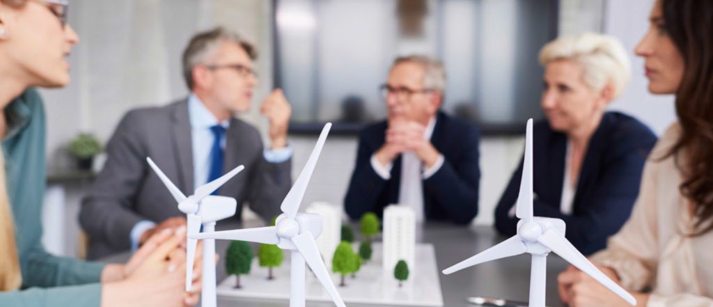 Business meeting with model wind farm on table