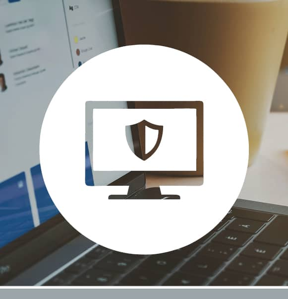 White monitor with shield icon overlaying a photo of a hands typing on a laptop