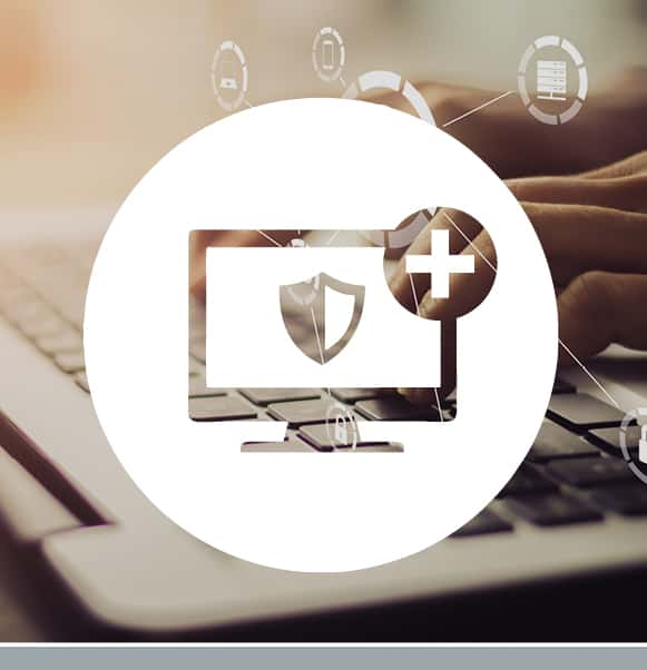 White monitor with shield and plus symbol icon overlaying a photo of a hands typing on a laptop