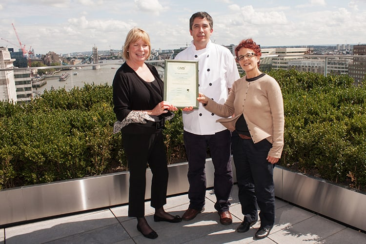 Two women and a man holding a certificate in a rooftop garden