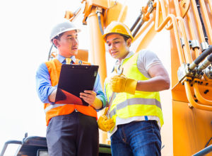 Two men wearing protective work wear in front of machinery