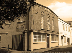 Sepia photo of old building QMS office
