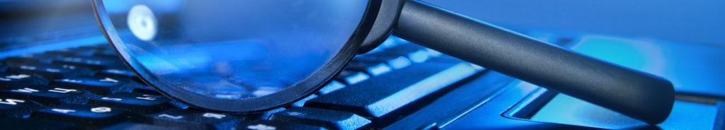 Magnifying glass on laptop keyboard