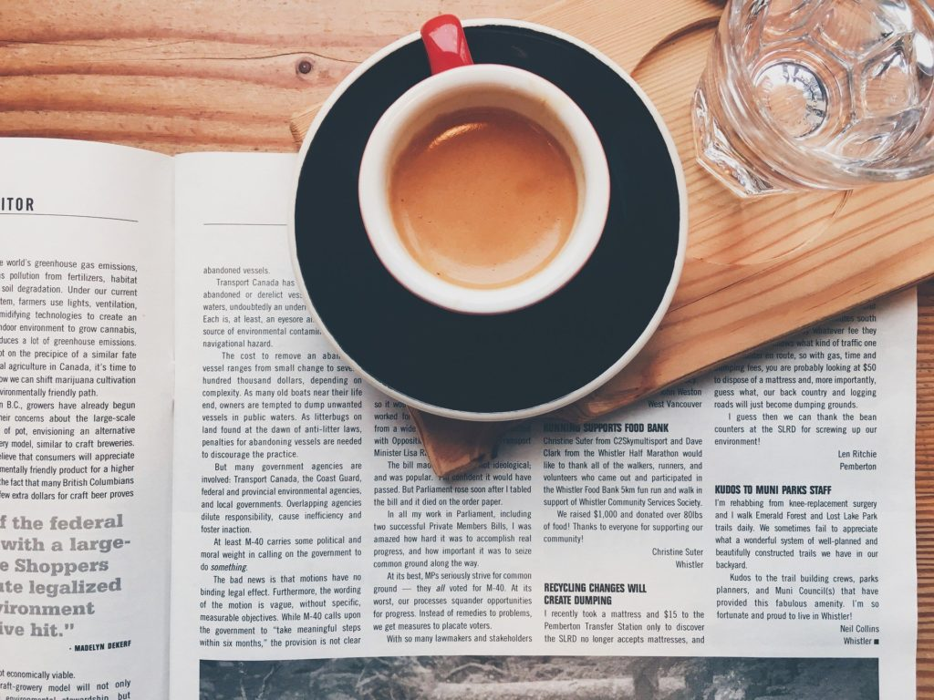 Cup of coffee on table with newspaper